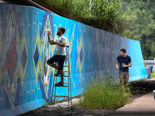 MIKE LAWRENCE / COURIER & PRESSArtist Matt Fitzpatrick (left) an art teacher at Newburgh's Castle High School and Jon Whitman a graphic designer at Shoe Carnival work on a 9 feet tall and 75 feet wide mural under the I-69 and U.S. 41 overpass recently. The mural, designed by Whitman, features Indiana's state seal, the peony as the state flower and the