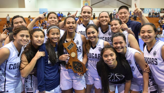 The Academy of Our Lady of Guam Cougars celebrate a victory over the Notre Dame Royals in the IIAAG Girls' Basketball League championship game at the Southern High gym on Dec. 18. The Cougars continue their streak with winning the Hardeman Showcase in Manila, Jan. 2016.