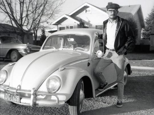 """The late Jim Jones stands with his Volkswagen Beetle, named """"Tortuga,"""" in the 1960s."""