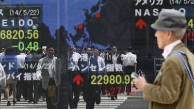 A passer-by looks at an electronic stock board of a securities firm in Tokyo, Friday, May 23, 2014. Japan's Nikkei 225 was up 0.9 percent at 14,473.19 after the dollar climbed to near 102 yen overnight.Thailandâ??s stock market sank Friday, a day after the countryâ??s military seized power in a nonviolent coup. Other world stock markets were mostly higher but Europeâ??s gains were tempered as a polarized Ukraine braced for weekend elections.