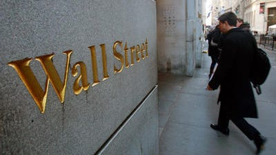 In this Oct. 2, 2014 file photo, Wall Street is etched in the facade of a building in New York's Financial District. U.S. and global stocks fell Tuesday as investors closed their positions ahead of the New Year and amid concern over political uncertainty in Greece.