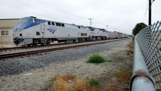 An Amtrak train passes through Vista Del Mar Drive near Seaward Avenue in Ventura. Union Pacific Railroad has dropped its application to legally have fences at several locations used by beachgoers.