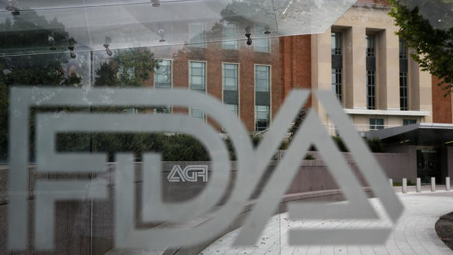 "FILE - This Aug. 2, 2018, file photo shows the U.S. Food and Drug Administration building behind FDA logos at a bus stop on the agency's campus in Silver Spring, Md.  In a report to Congress and an accompanying ""playbook"" for states and localities, key federal health agencies and the Defense Department sketched out complex plans for a vaccination campaign to begin gradually early next year or later in 2020, eventually ramping up to reach any American who wants a shot. The Pentagon is involved with the distribution of vaccines, but civilian health workers will be the ones giving shots."