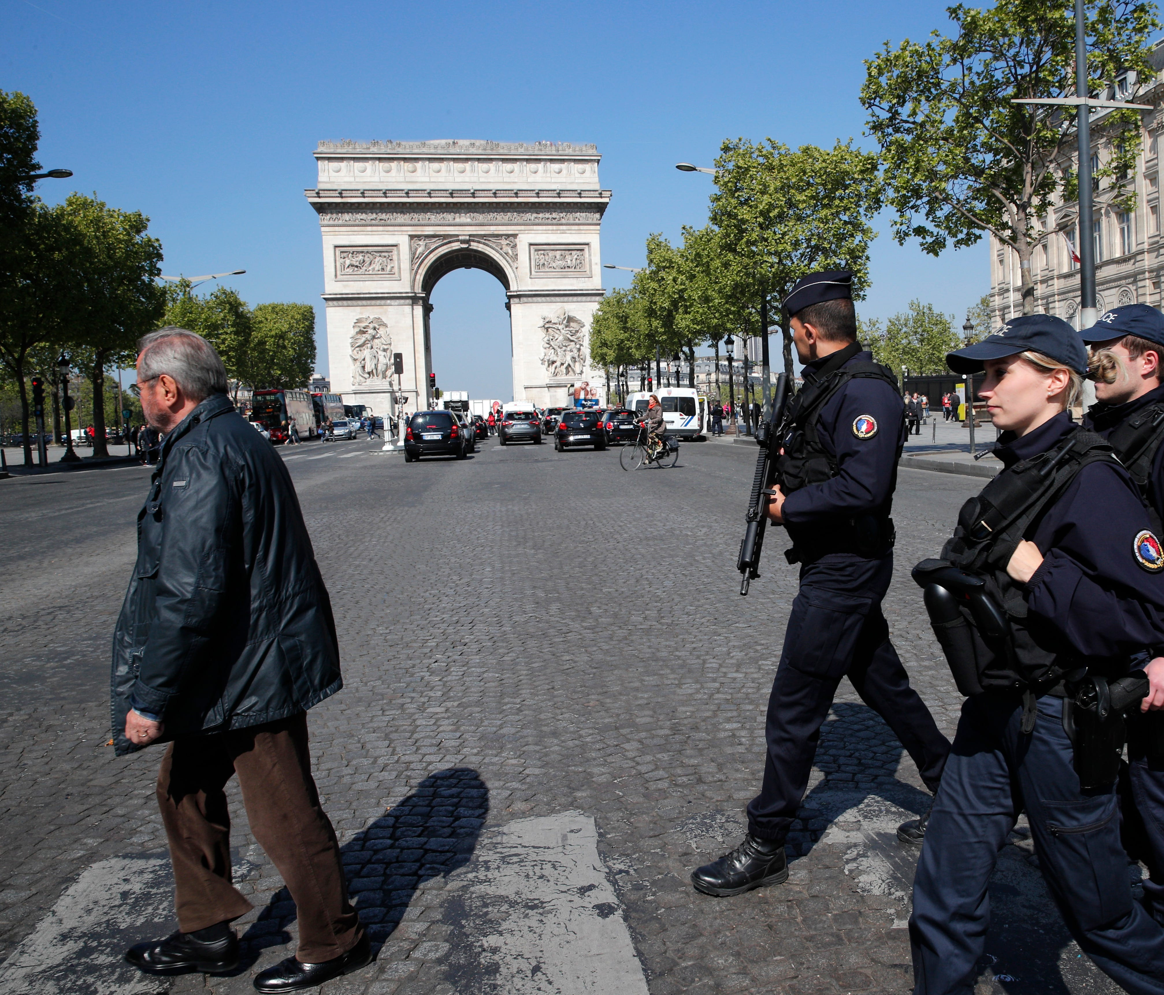 Police officers patrol on the Champs Elysees boulevard in Paris, Friday, April 21, 2017.