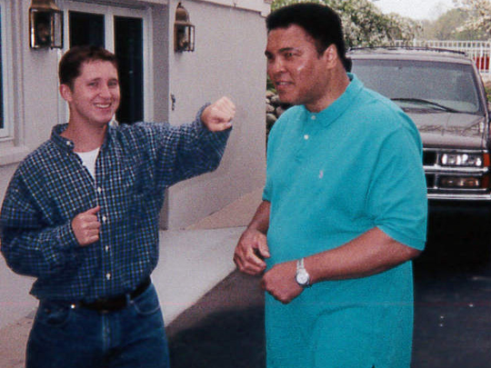 Andy Schiek playfully interacts with Muhammad Ali.