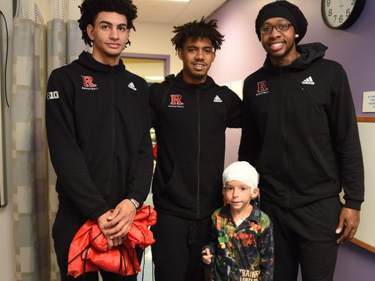 Brady Hill, who turns eight years old next Thursday, was delighted to show his transformers to members of the Rutgers Men's Basketball Team,  Geo Baker, Corey Sanders, and Deshawn Freeman, during their visit with pediatric patients and their families at RWJBarnabas Health's Saint Barnabas Medical Center