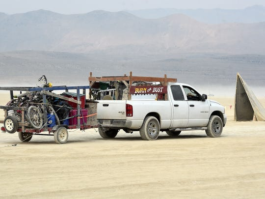 A heavily loaded pickup pulls a trailer out of the Burning Man encampment on Monday, Sept. 4, 2017, during the annual departure event known as Exodus.
