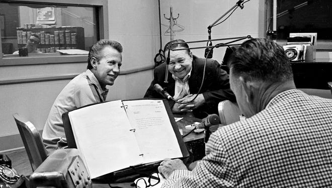 """Guest Porter Wagoner, left, and Tex Ritter, center, co-host of WSM-Radio's """"Opry Star Spotlight,"""" look at co-host Grant Turner as he gives a station identification June 22, 1965."""