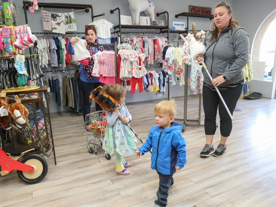 Tiffany Page, right, watches her son Henry as Kelly McDaniel, left, watches her daughter Caroline while they shop at JadaBug's Kids Boutique in La Quinta, February 23, 2018.