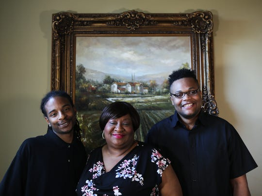 May 11, 2018 -- Yolanda Tate is flanked by her former foster children, Marquez Hardaway, left, 25, and Devonta Tate, 24, during a portrait shoot in their home on Friday. Tate has spent much of her life as a foster mother to teenage boys.