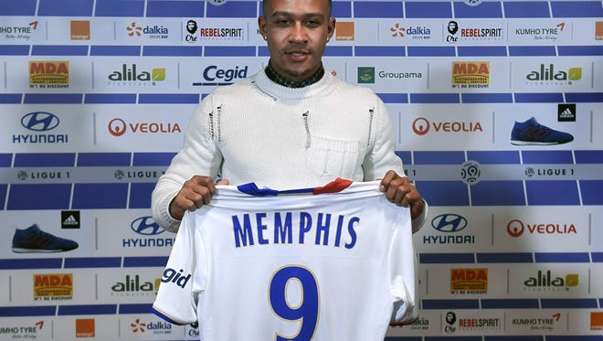 Depay poses with his new Lyon jersey.
