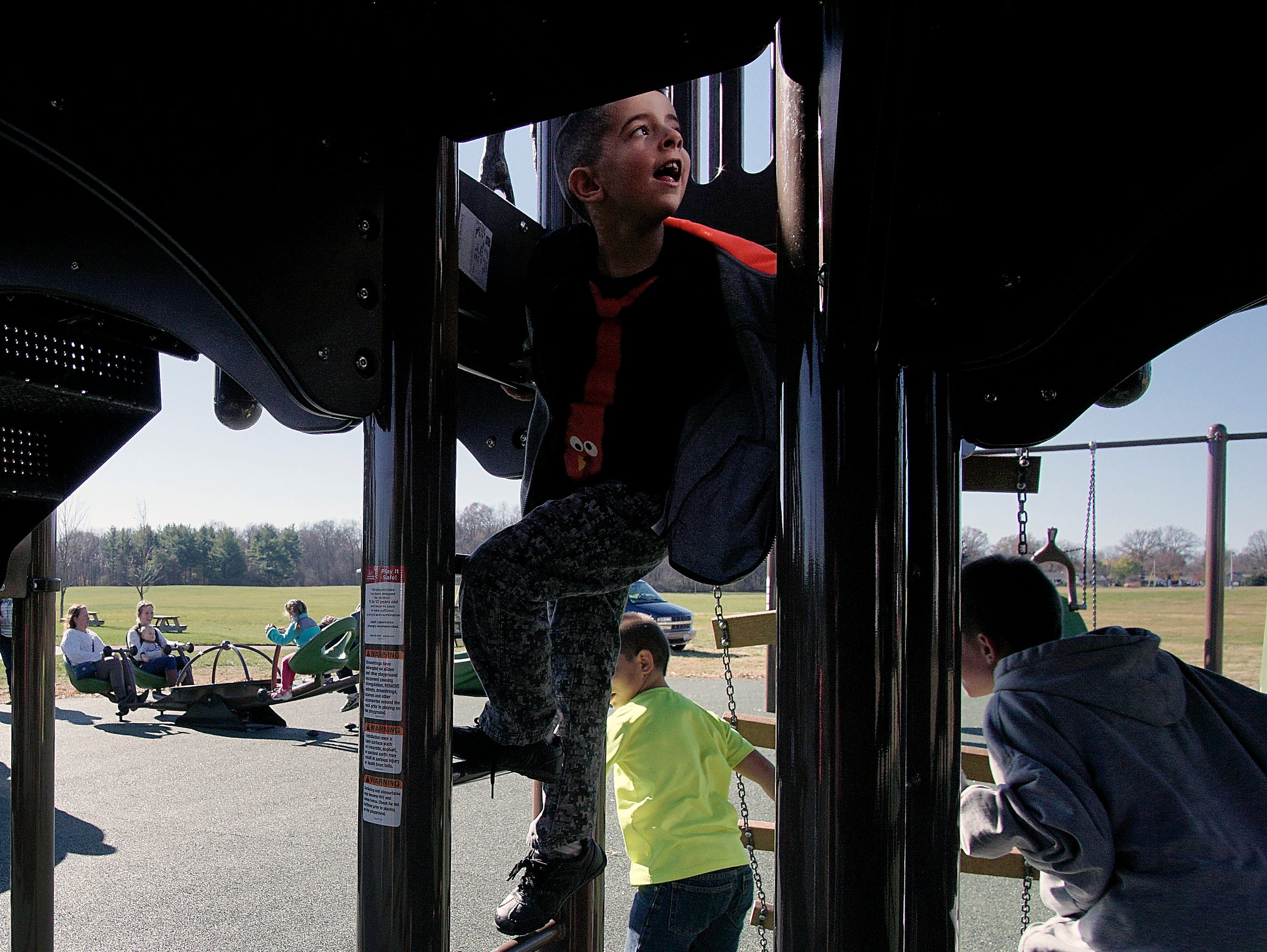 Kids climb, run and seesaw Sunday  during the opening