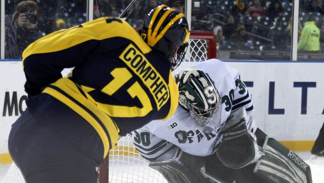 Michigan State goalie Jake Hildebrand, right, blocks shot by Michigan's JT Compher in first period of the  the Great Lakes Invitational consolation game at Comerica Park in Detroit on Dec. 28, 2013.