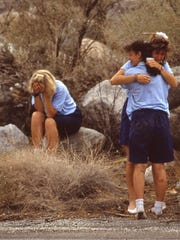 Tiia Thuren of Finland sits with her head down while Ginger Hogg of State College, Penn., hugs Tracy Rizzo of Levittown, N.Y. (facing), following the July 31, 1991, girl scout bus crash.