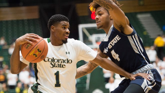 Antwan Scott, CSU's leading scorer last season, drives against Utah State's Shane Rector during a Jan. 16 game at Moby Arena. Scott had a pre-draft workout Friday with the Denver Nuggets.