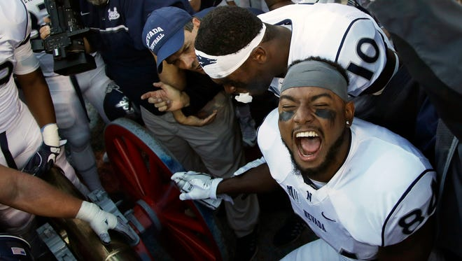 Nevada wide receiver Jerico Richardson celebrates as he spray paints the Fremont Cannon after an NCAA college football game against UNLV, Saturday, Nov. 26, 2016, in Las Vegas. Nevada won 45-10. (AP Photo/John Locher)
