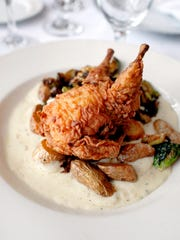 Country-fried quail stuffed with a house sausage dressing, bourbon peppercorn gravy, potato of the day and crispy Brussels sprouts at Buck's Restaurant and Bar in Old Louisville.