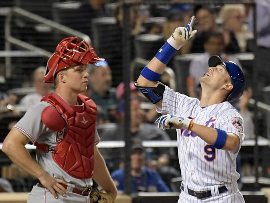 New York Mets' Brandon Nimmo, right, gestures as he comes home after hitting a home run while Cincinnati Reds catcher Stuart Turner looks on during the fifth inning of a baseball game Thursday, Sept. 7, 2017, in New York.