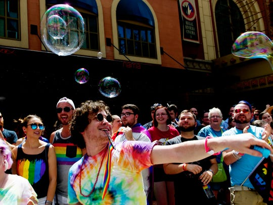 Daniel Basham, of Knoxville, blows bubbles in the crowd during the annual Knoxville Pridefest Parade in downtown Knoxville on Saturday, June 17, 2017.