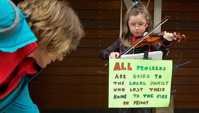 A passerby drops money into a donations jar in July as Sophie Nylen, 8, plays her violin to raise money for home fire victims in Juneau, Alaska. Sophie raised $1,787.24 in six days and gave it to relatives of a family whose home had burned.