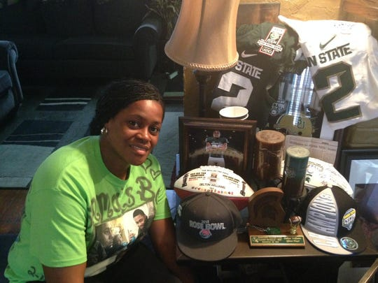 Jennifer Evans, mother of Delton Williams, shows off her son's memorabilia at her home in Erie, Pa. Evans said her son's decision to stay at MSU was an easy one to make.