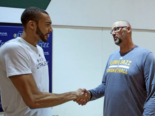 Former Utah Jazz player Greg Ostertag, right, shakes hands with Utah Jazz player Rudy Gobert during media interviews at the Jazz practice facility Wednesday, March 22, 2017, in Salt Lake City.