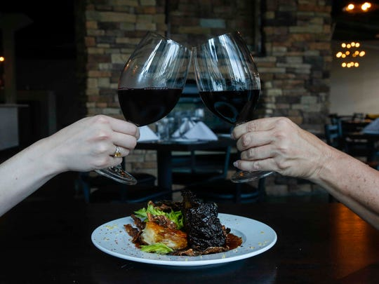 A toast over lacquered short ribs, lemon-thyme potato and celery root napoleon, and a red wine reduction at Salt of the Hearth restaurant, opening at West Glen in West Des Moines.