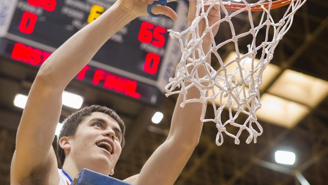 Jackson's Jake Byers, who hit the winning free throw to defeat McKinley 66-65 in double overtime during the 2018 district championship at Memorial Civic Center, cuts the net.