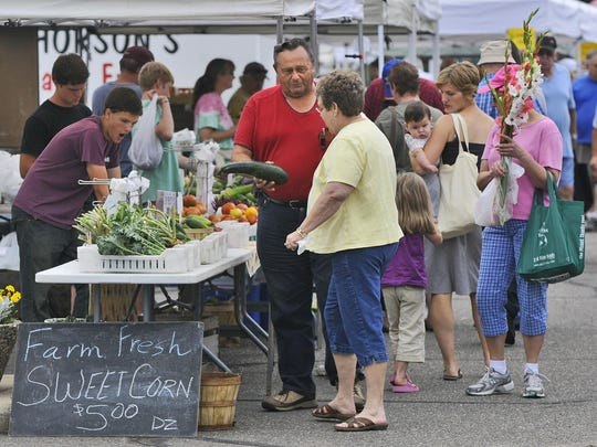 Customers peruse the vegetables, flowers and other items available during the St. Cloud Farmers Market.
