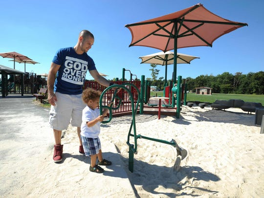 Christopher Johnson of Lincoln helps his son Giovanni (3) with the hand digger in the sandbox at the Milford Can-Do playground.