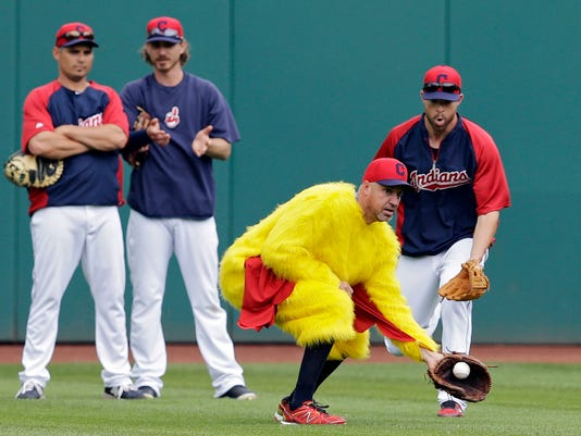 Cleveland Indians relief pitcher Scott Atchison, center, shags balls in a chicken costume in front of starting pitcher Corey Kluber, right, during batting practice before a baseball game against the Los Angeles Angels, Wednesday, June 18, 2014, in Cleveland. (AP Photo/Mark Duncan)