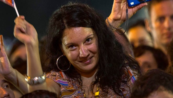 A young Cuban woman waves a flag of her country during a concert of Silvio Rodriguez in Havana, Cuba, Saturday, Dec. 20, 2014. For a generation that grew up believing the best way to pursue their dreams was to leave the island, the announcement this week that Cuba will open relations with the U.S. is prompting many to reevaluate their futures. Also, Cuban-Americans are considering what the changes will mean for their lives, whether they are significant enough to present a once far-fetched chance for them to return. (AP Photo/Ramon Espinosa)