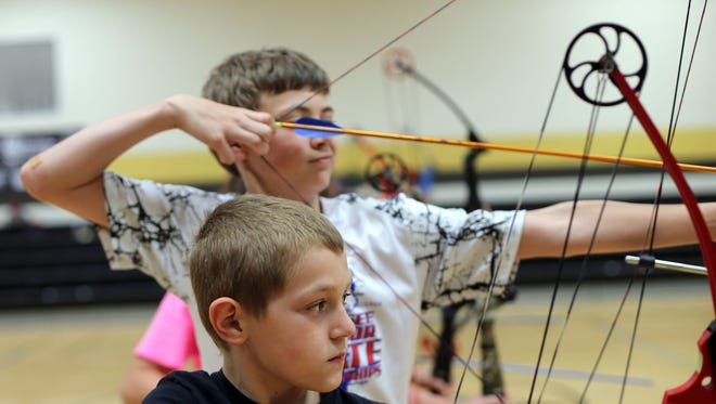 Archery club members Cian Hester, back, and Jacob Austin shoot at targets after school at Christiana Elementary in May 2015.