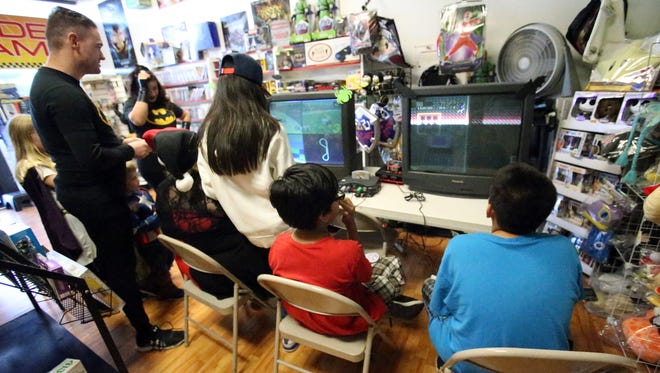 Patrons at One More Level Retro Gaming at 10968 Montwood play classic games on systems that have been set up inside the store. Though new systems, like PlayStation and Nintendo, rule the gaming world, the original arcade games and older consoles are making a comeback