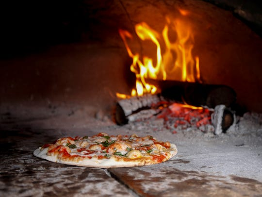 A pizza bakes in a brick oven at Parlo Pizza during