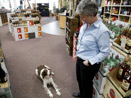Julie Crowley and her dog, Cuppa Joe, hang around on the floor of Triphammer Wine and Spirits in Lansing.