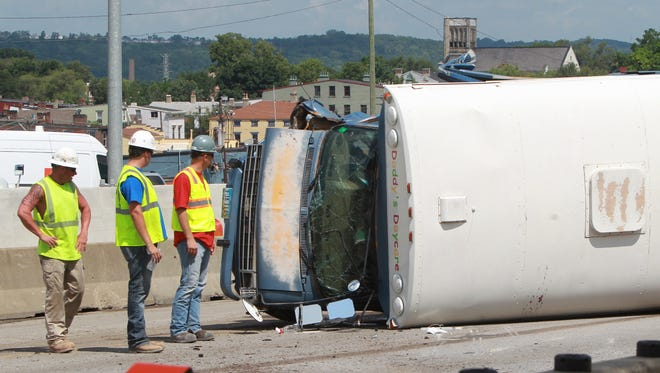 Workers look over an overturned daycare bus blocking the Hopple Street ramp from Interstate 75.