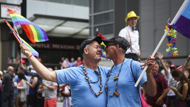 Jeff and Rob Green of Covington, KY celebrate their relationship of 32 years and marriage of 2 years during the Cincinnati Pride Parade Saturday morning. Sat. June 27, 2015.