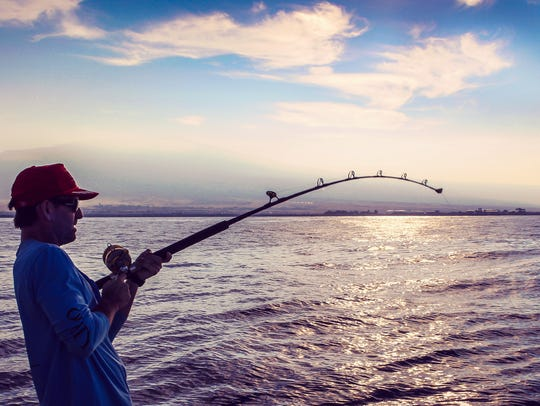 Man with fisher rod in almost silhouette against a