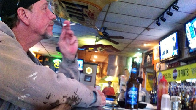 Tad Thompson, 57, Greenwood, smokes a cigarette Monday at the Blind Pig bar in downtown Greenwood, where he's been a regular for about a year. Starting January, Thompson and other smokers will be unable to smoke there under a new Johnson County ordinance that bans smoking in all bars and other locations.