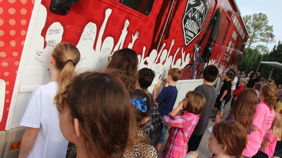 """Children signing the """"Riding It Forward"""" RV and pledging to live a healthy lifestyle."""