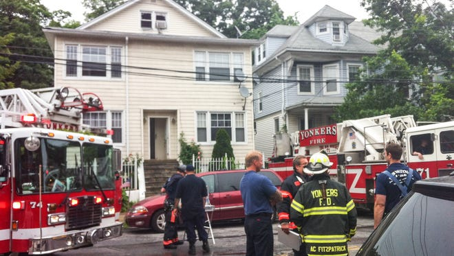 Firefighters at the scene of a fire at 112 McLean Ave. in Yonkers on Thursday, June 12, 2014. Two firefighters suffered minor injuries. The fire started on the top floor of the 2 1/2 -story house. It displaced eight adults and eight children.