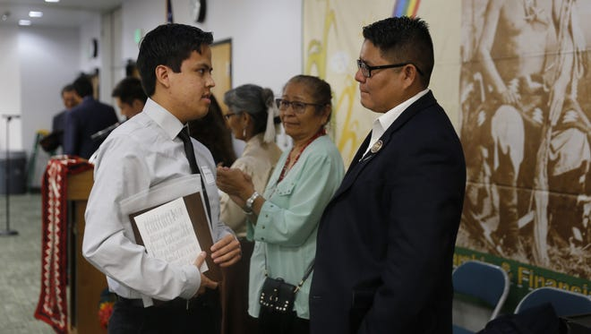 Kirtland Central High School graduate Randall R. Marshall, left, talks to Navajo Nation Council Delegate Nathaniel Brown after receiving the Chief Manuelito Scholarship in Farmington during an event in July.