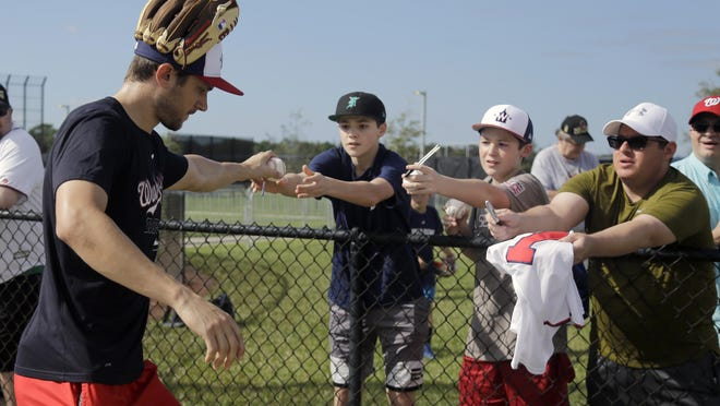 Washington Nationals shortstop Trea Turner hands a ball back to a fan after signing it last month during spring training in West Palm Beach.