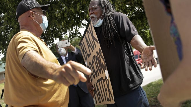 Veteran Johnnie Neil, left, and protester James Shelby have a discussion outside the Kansas City Veterans Affairs Medical Center. Civil rights organizations are pushing for changes at the hospital after numerous complaints from Black employees about harassment and discrimination.