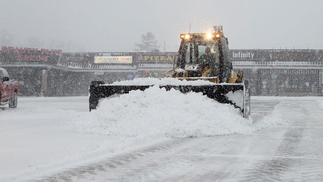 A bucket loader equipped with a snow plow clears the parking lot of the Clarkstown Plaza in New City.