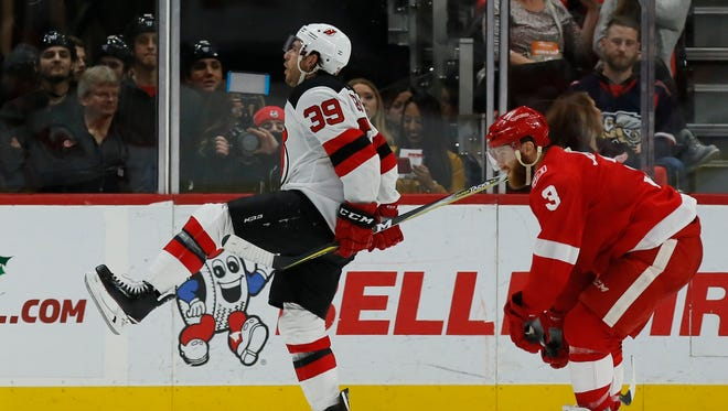 New Jersey Devils left wing Brian Gibbons celebrates his winning goal in overtime as Detroit Red Wings defenseman Nick Jensen skates past on Saturday night.