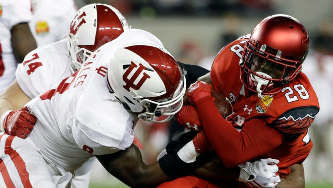 Utah running back Joe Williams (28) is tackled by Indiana's Tegray Scales during the first half of the Foster Farms Bowl, Dec. 28, 2016, in Santa Clara, Calif.