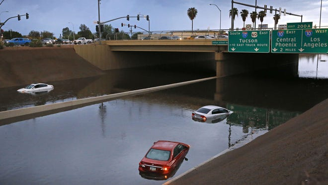 Cars sit stranded in flood waters along Interstate 17 (near Indian School Road) on Tuesday, Aug. 2, 2016, in  Phoenix.
