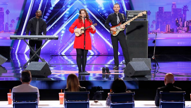 """In this undated photo provided by NBC, Mandy Harvey sings during auditions for the show """"America's Got Talent"""" in Pasadena, Calif. Harvey, a deaf singer is moving on to the semifinals of """"America's Got Talent"""" after delivering a performance that aired Tuesday, June 6, 2017, that judge Simon Cowell calls """"one of the most amazing things"""" he's ever seen or heard. Mandy Harvey told the judges on the NBC reality competition that she suffers from a connective tissue disorder and she lost her hearing when she was 18. Now 29, Harvey said she taught herself to sing again using muscle memory and visual tuners."""